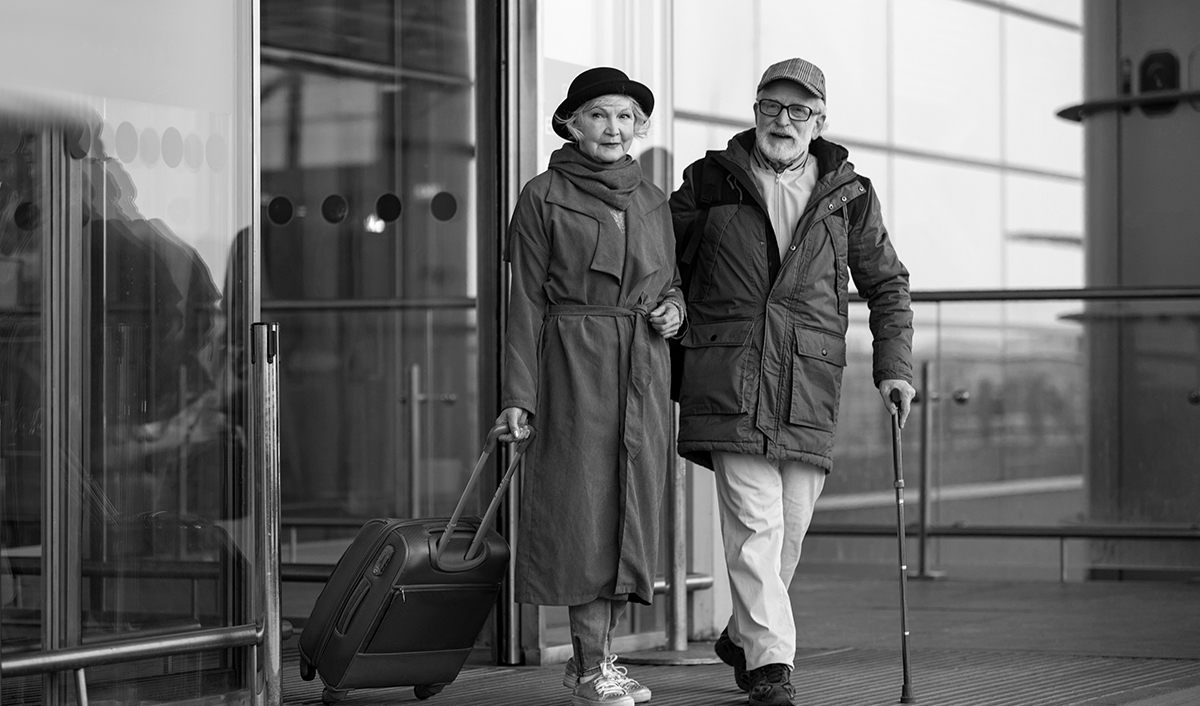 Senior couple at airport traveling with suitcase and cane