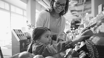 Woman shopping for fruit with little girl