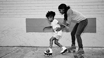 Mother helping son to roller skate