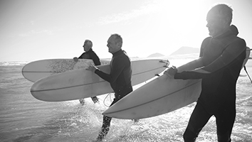 Three older men with surfboards