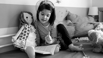 Young girl reading book with a doll